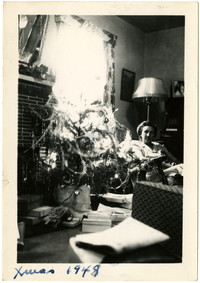 Woman seated next to Christmas tree in living room