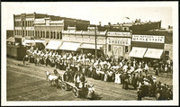 Spectators line Railroad Avenue, downtown Bellingham, Washington, as uniformed men on white horseback parade past.