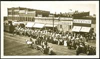 Spectators line Railroad Avenue, downtown Bellingham, Washington, as uniformed men on white horseback parade past.