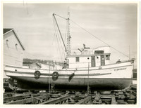 """Wooden boat named """"Cloverleaf"""" in dry dock in Fairhaven, Washington, with South Hill in the background."""