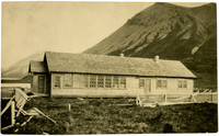 Exterior of simple, one-story school house in remote, mountainous location