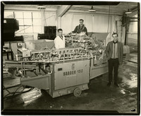 Three men with the Baader 150 and other fish processing equipment