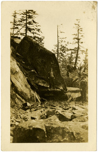Two men stand in front of rock outcropping that appears to be blocking road construction