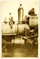 Three boys pose atop the boiler and inside the smoke stack of a steam engine that has colided with a larger engine