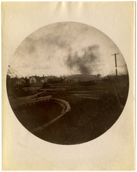 Railroad through lumber yard with houses in background