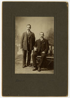 Studio portrait of two unidentified men in suits, one seated, one standing