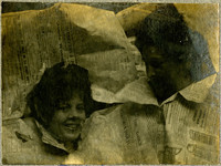 Two women jovially peer through holes in sheet of newspaper