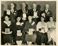 Local authors - Five seated women and four men standing behind them, dressed for special occasion, holding published works