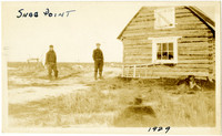 Two men stand next to log cabin at Snag Point, Alaska