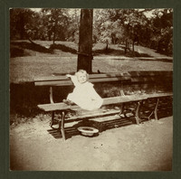 Unidentifed baby in white dress on park bench