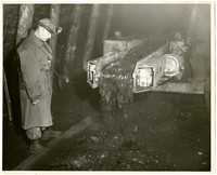 Man in trenchcoat and headlamp stands in coal mine, watching coal chute in operation