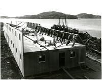 Raising a building as part of the Pacific American Fisheries facility at Alitak, Kodiak Island, Alaska