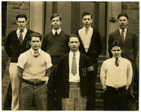 Seven young men in sweaters and ties pose in two rows on the steps outside a building