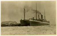 """Two large steamships, the """"Cordova"""" and the """"Victoria"""", moored at pier in icy and snow-covered waters"""