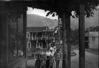 Three women, a man and a boy walk toward camera in front of Hotel Glacier in Glacier, WA