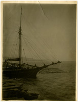 Part of sailing vessel near dock in Bellingham Bay, with log boom behind and cut lumber on dock in foreground