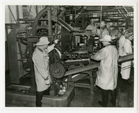 Unidentified salmon processing machine with four men in wet gear examining it in processing facility with line of workers to right