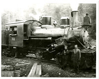 Two men lean next to a steam locomotive while two men lean out of the cab, with forest in background