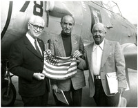 Three unidentified  elderly men pose before a military fighter airplane, holding a small American flag