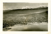Aerial view of Bellingham with the harbor in the bottom foreground, the downtown in the middle ground with Lake Whatcom beyond, and Mt. Baker in distance