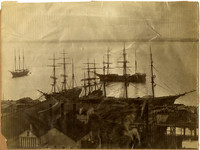 Five three-masted sailing wait offshore or at Sehome dock for loads of lumber
