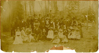A group of men, women, children gather for photograph in forest clearing