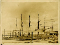 Two large, multi-masted vessels moored at pier with float of logs in foreground
