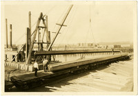 Steam-powered crane or pile driver lifts beams from rail car at Bellingham Bay T Mill
