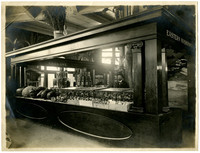 Agricultural displays from Eastern Washington and Spokane, as listed on entablature above booths, in exhibition hall