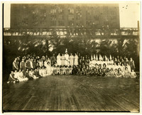 Large group of women and girls in costumes pose in semi-circle on outdoor wooden stage