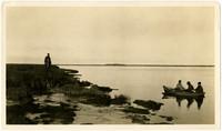 Three men in rowboat on Nelson River, Alaska, one man standing on marshy shore