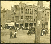 """View from across intersection of three-story stone building called """"The Sunset Block"""" with groundfloor storefronts, with a small band playing a circus-type contraption on corner as people mill about"""