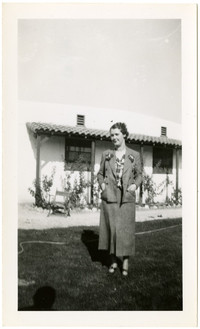 Woman stands on lawn outside Spanish style bungalow