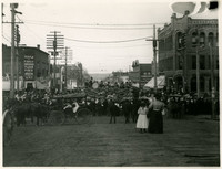 View down unpaved Holly Street, Bellingham, Washington, with crowd gathered to watch approaching parade float