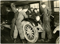 Five mechanics working on automobile engine