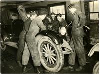 Five mechanics working on automobile engine