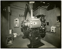 The interior of a theater projection room with a large film projector bolted to the floor.