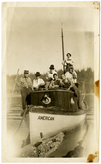 """Several people pose on deck of small vessel """"American"""""""
