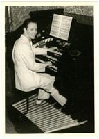 Gunnar Anderson smiles over his shoulder while seated at large electric organ with multiple foot pedals