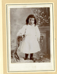 Young girl in white dress poses standing next to chair in studio portrait