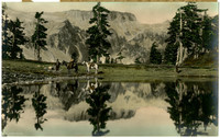 Hand tinted image of four men, two on horseback, next to a lake with a flat-topped promontory in the distance