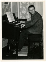 Gunnar Anderson smiles over his shoulder while seated at organ