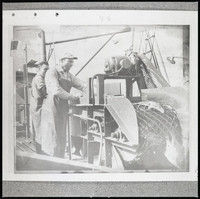 Two unidentified men in long aprons standing by a large machine (fish packing operation)