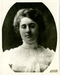 Portrait of unidentified young woman in lacey, high-necked gown, upswept hair