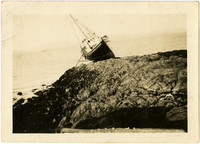 Bow and starboard view of fishing vessel run aground on rock at high tide