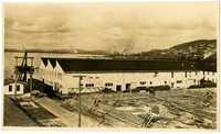 Three large, white, connected warehouse or cannery buildings on the Fairhaven waterfront with South Hill downtown Bellingham, WA, waterfront on left