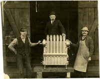 Knute Evertz and two other men pose next to a 'portable' steam radiator made from cast metal