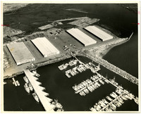 Aerial view of fishing boat marina, breakwater, waterfront warehouses, and log floats