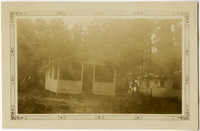 Small clapboard cabin with porch in woods, with another cabin nearby