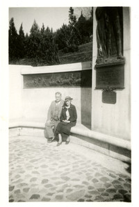 A man and woman sit on bench along wall of monument, Washington, D.C.